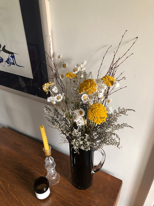 yellow achillea and beeswax candle